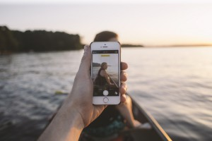 L'image montre une smartphone tenue par un canotier au milieu d'un lac.
